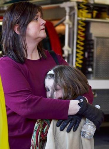 A mother holds her daughter at Sandy Hook Elementary School in Newtown, Conn.